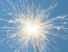 Close up of a burning sparkler on a blue background