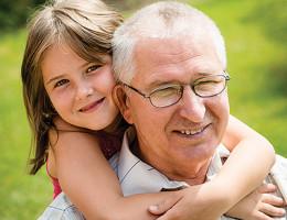 Outdoor lifestyle portrait of grandchild hugging grandfather