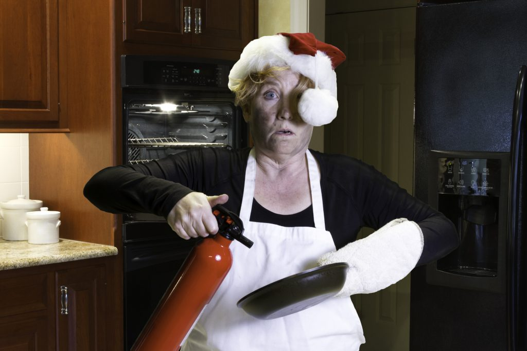 Mature woman with singed face holding pan and fire extinguisher with santa hat and apron standing in kitchen.
