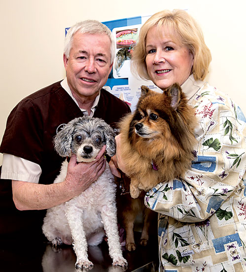 "Dr. Robert Reuther, holding Amy, and receptionist Kathy Medonis with Rudy, who ""works"" with Kathy at the clinic."