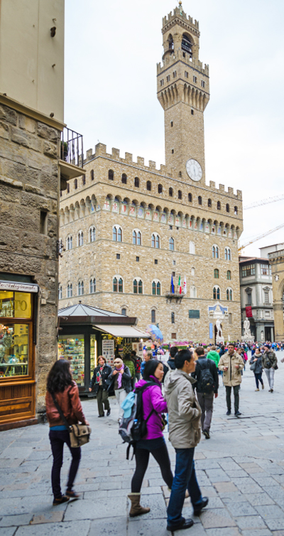 Tourists walking and admiring Palazzo Vecchio in Florence.
