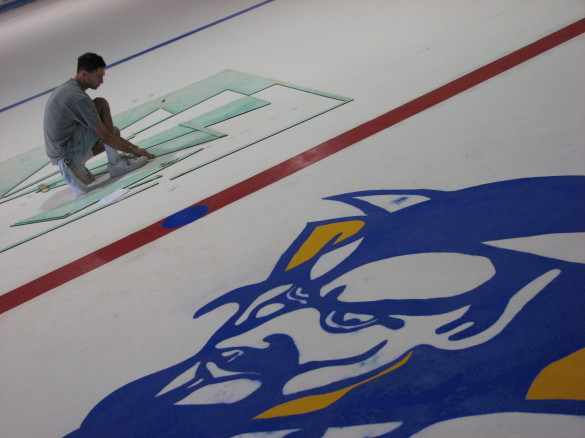 The old way of getting lines and logos on the ice? Painting. It took forever and it was maddening. Plastic logos make today's rebuild of the ice much easier.