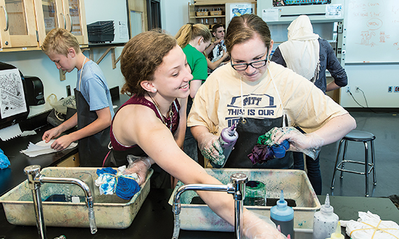 Julianne Jenkins ,left, and Riley Debski put the finishing touches on tie-dye t-shirts they made in a chemistry lab. The lab provides students with an engaging and colorful way to study the covalent bonding of molecules.