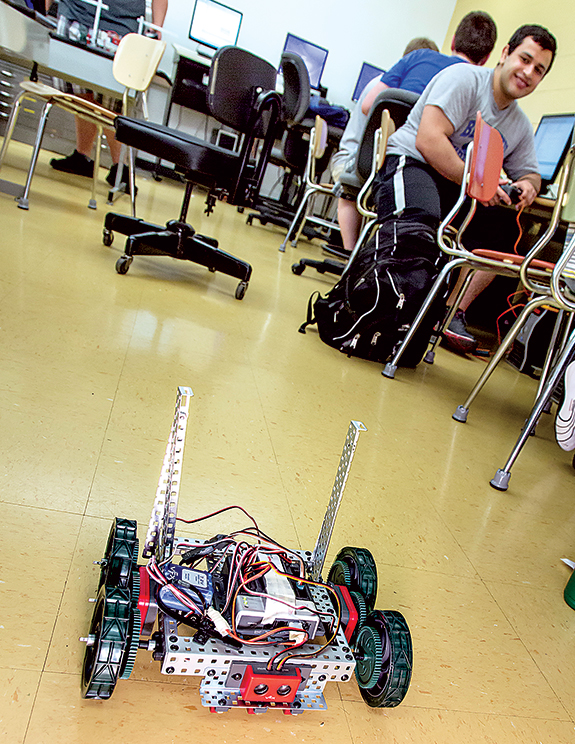 Zeynul Zaynullaev tests a fully automated robot he designed and built. The robot is equipped with proximity sensors to prevent collisions.