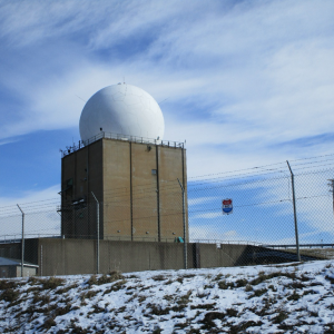 A large white sphere with antennas sticking out the sides and top sits on top of a tall rectangular structure behind a chain-link fence. This is the Nike Missile Site.
