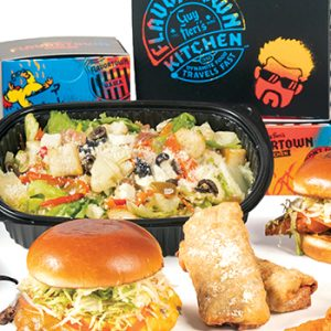A spread of food from Guy Fieri's Flavortown Kitchen, including a salad, burger and chicken sandwich, placed in front of a colorful branded delivery box. A spread of food from Guy Fieri's Flavortown Kitchen, including a salad, burger and chicken sandwich, placed in front of a colorful branded delivery box.