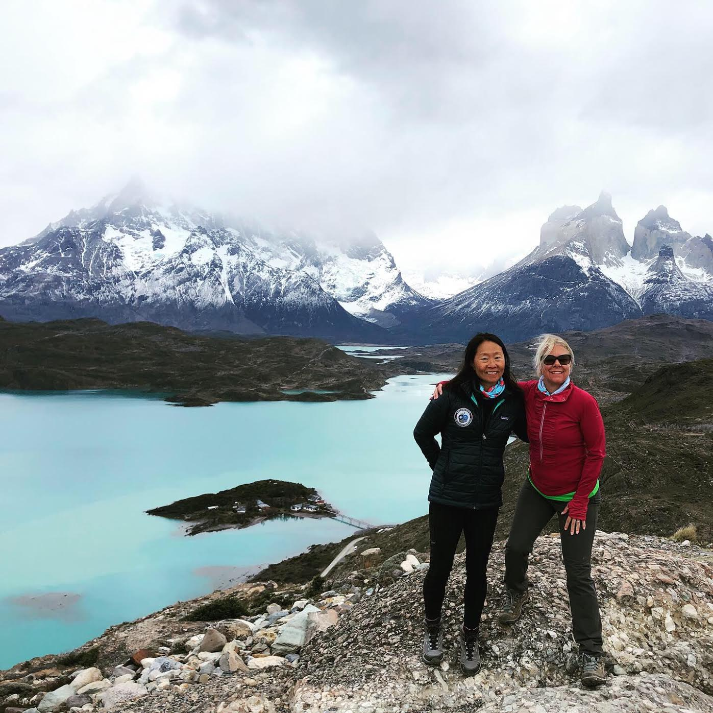 Carolyn Newkirk and her friend Bernadette pose in front of the aqua-blue Lake Pehoé and foggy mountains in Patagonia.