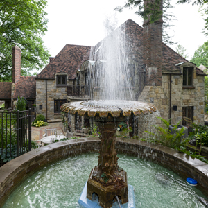 A stone fountain sends streams of water into the air in front of the large stone house on Roycroft Avenue.
