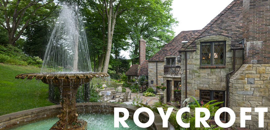 A big fountain with a house behind it and trees to the left of the house