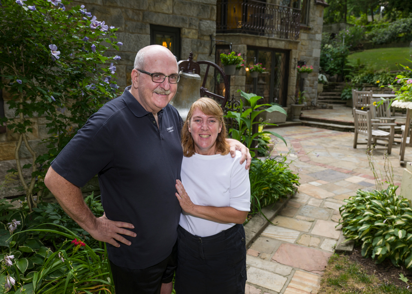 John and MaryAdele Krolikowski standing on the patio in front of their house with vegetation around them.