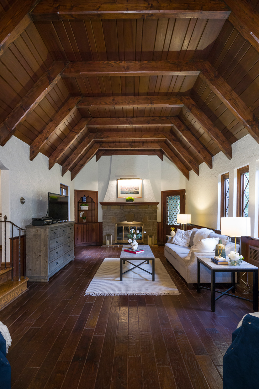 A big living room with dark wood floors and dark wood slanted cerilings and modern furnishings.