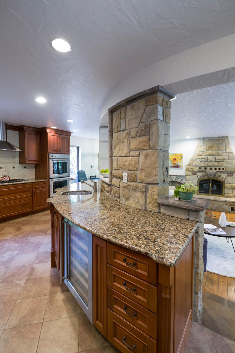 A kitchen with a curved counter and tan floor tiles. It is well lit with a fireplace in the livingroom in the background.