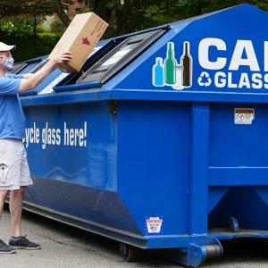 A man wearing a mask places a cardboard box in a PRC recycling bin.