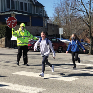 A crossing guard stops traffic as two young students cross Washington Road near Westminster Presbyterian Church.