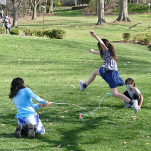 Three young girls wearing masks and playing jump roap in Main Park.