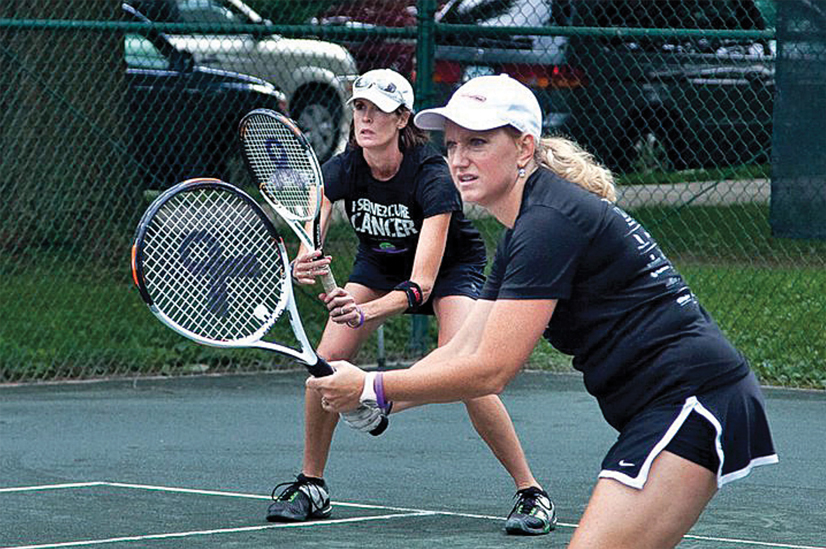 two women playing tennis on a tennis court.
