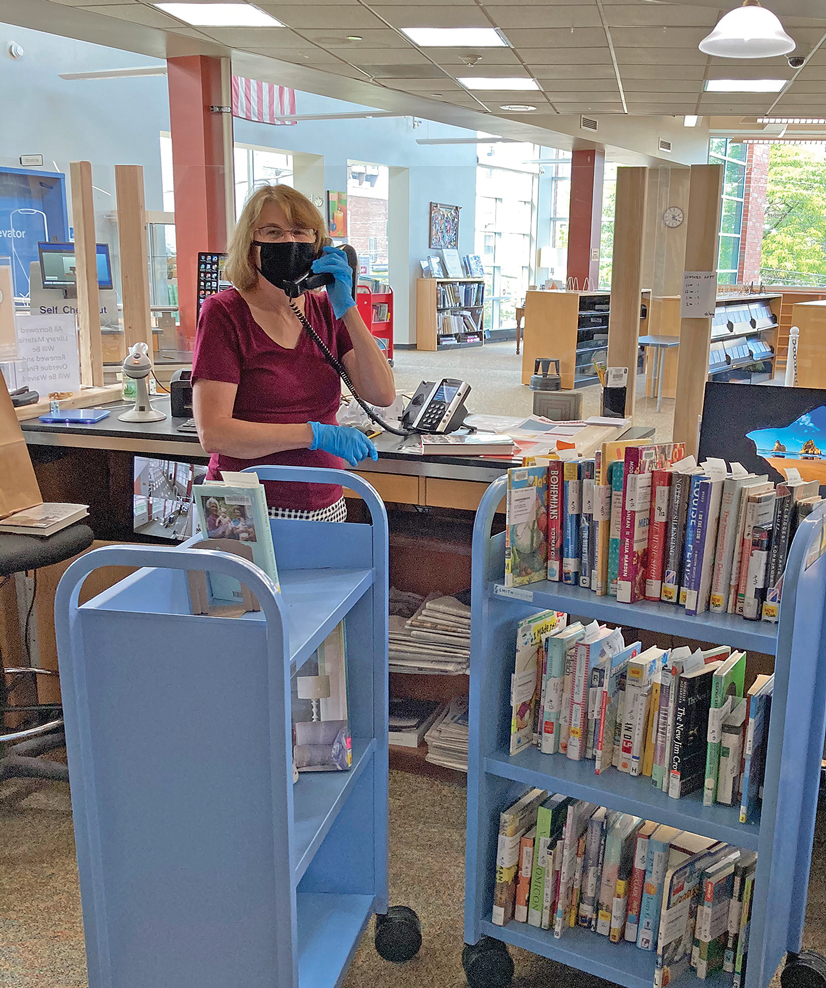 A woman standing behind a desk in the library on the phone wearing a mask.