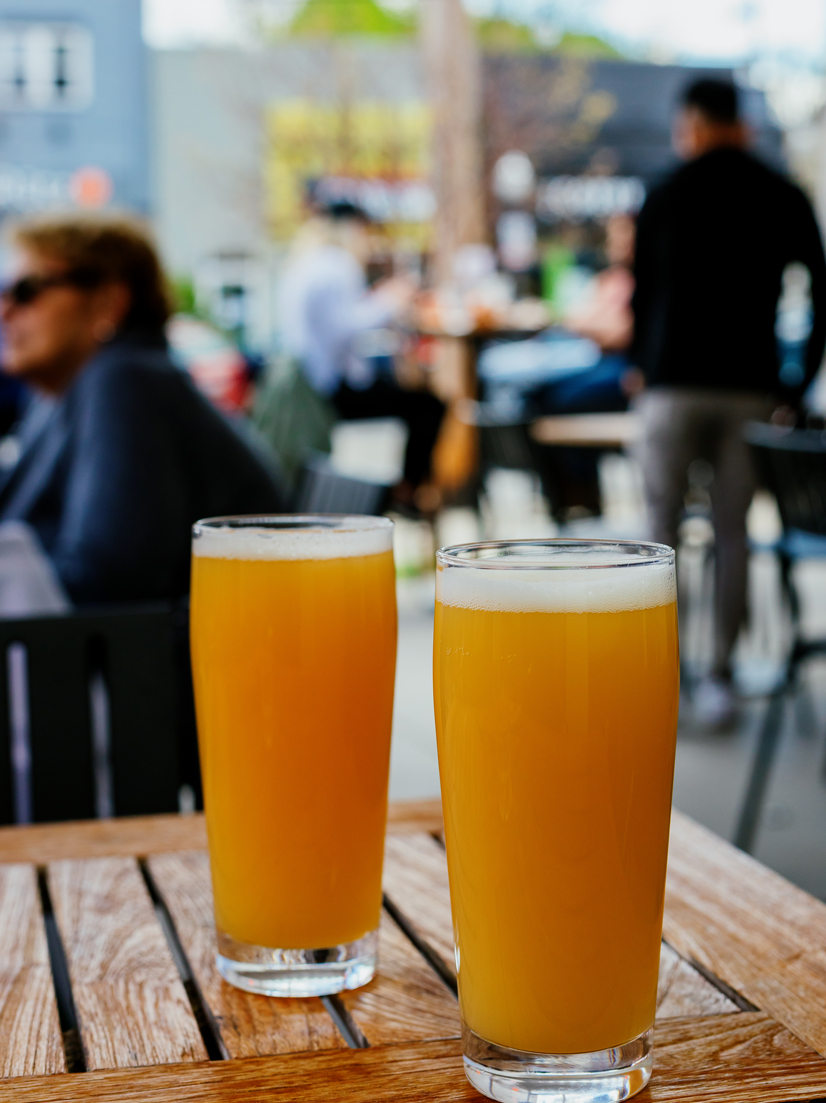 Two beers in glasses sitting on a table at a restaurant outside.