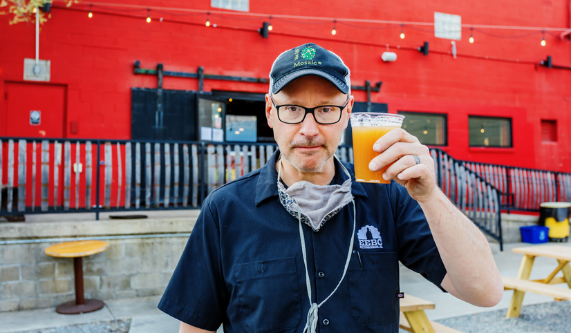 Scott Smith, owner of east end brewing, holding a beer outside in front of his brewery.