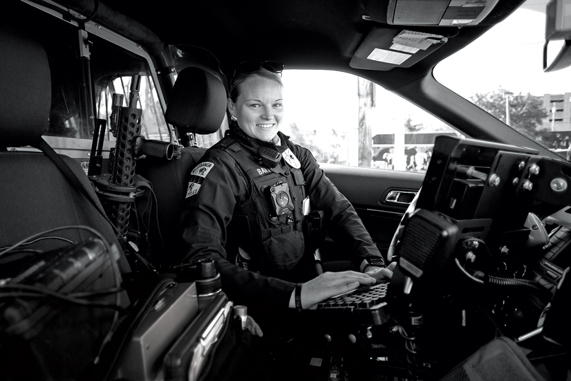 Officer Hayley Barto in police uniform in police car.