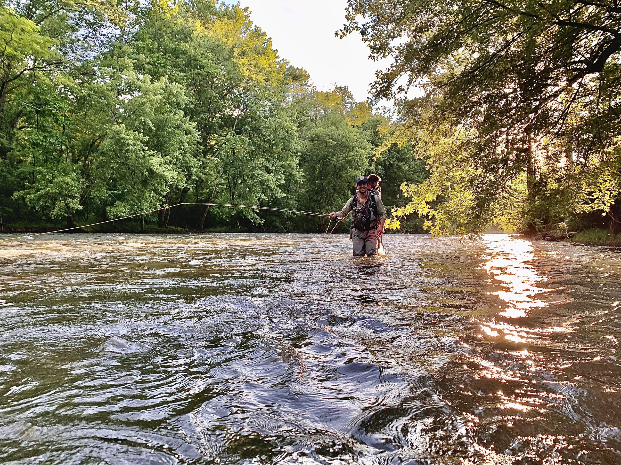 A man stands knee-deep in a river, flyfishing with the sun overhead and his daughter on his back..