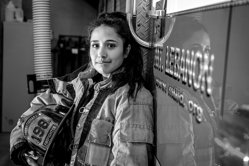 Portrait of Cecilia Smith in firefighter uniform leaning against firetruck in firestation.