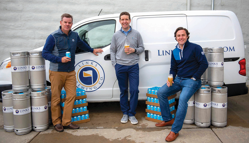 Three men, owners of Links Brewery, standing in front of van with kegs around them.