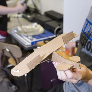 A student shows off a cardboard airplane.