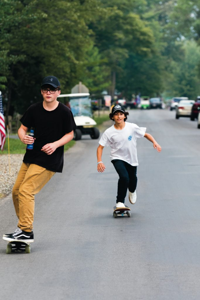 Two teenagers ride skateboards through a campground.