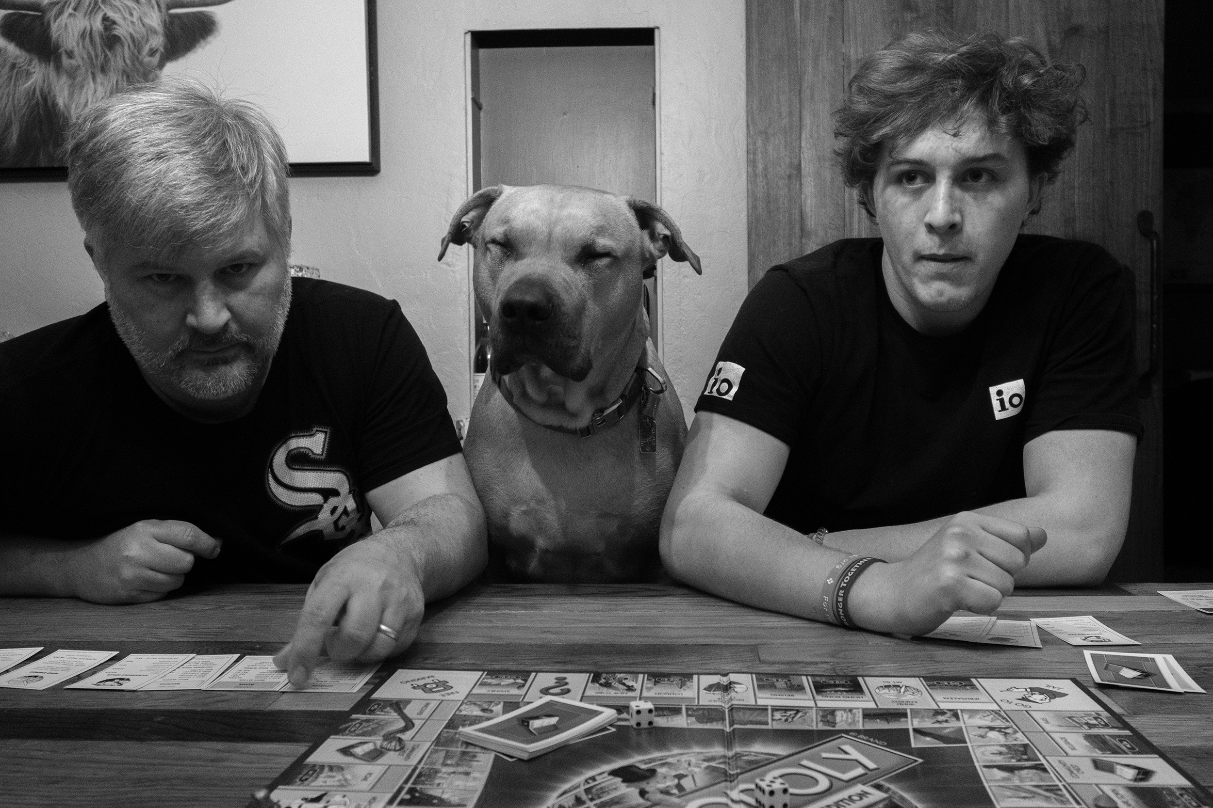 A happy pitbull sits at the table, sandwiched between two Kubit family members playing Monopoly.
