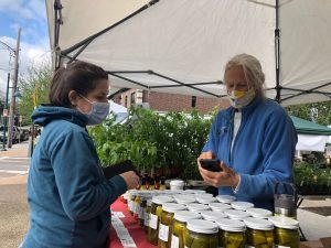 A woman purchases pickles from another at the Mt. Lebanon Uptown Market on May 8.