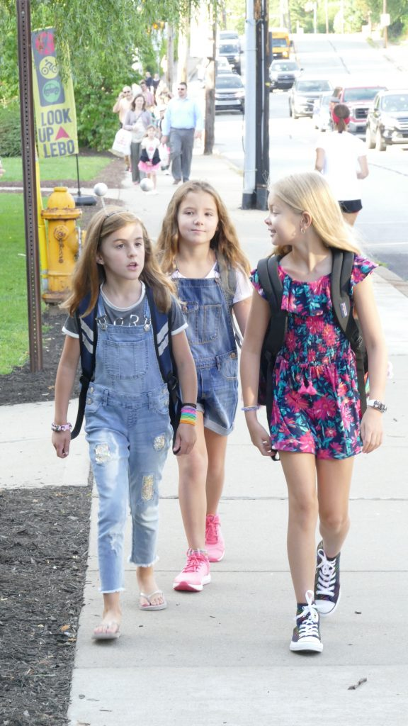 Three young students walking to school.