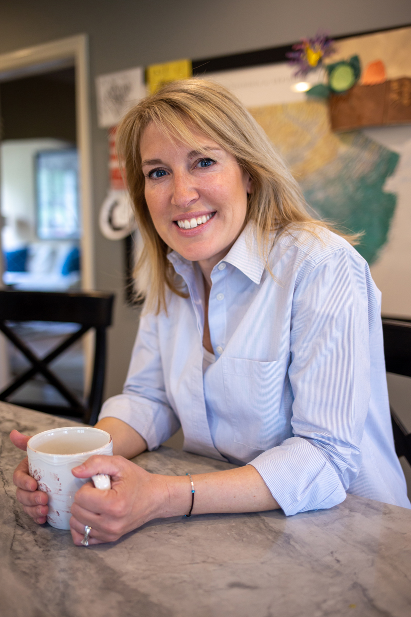 Danielle Deemer holding a cup of coffee smiling.