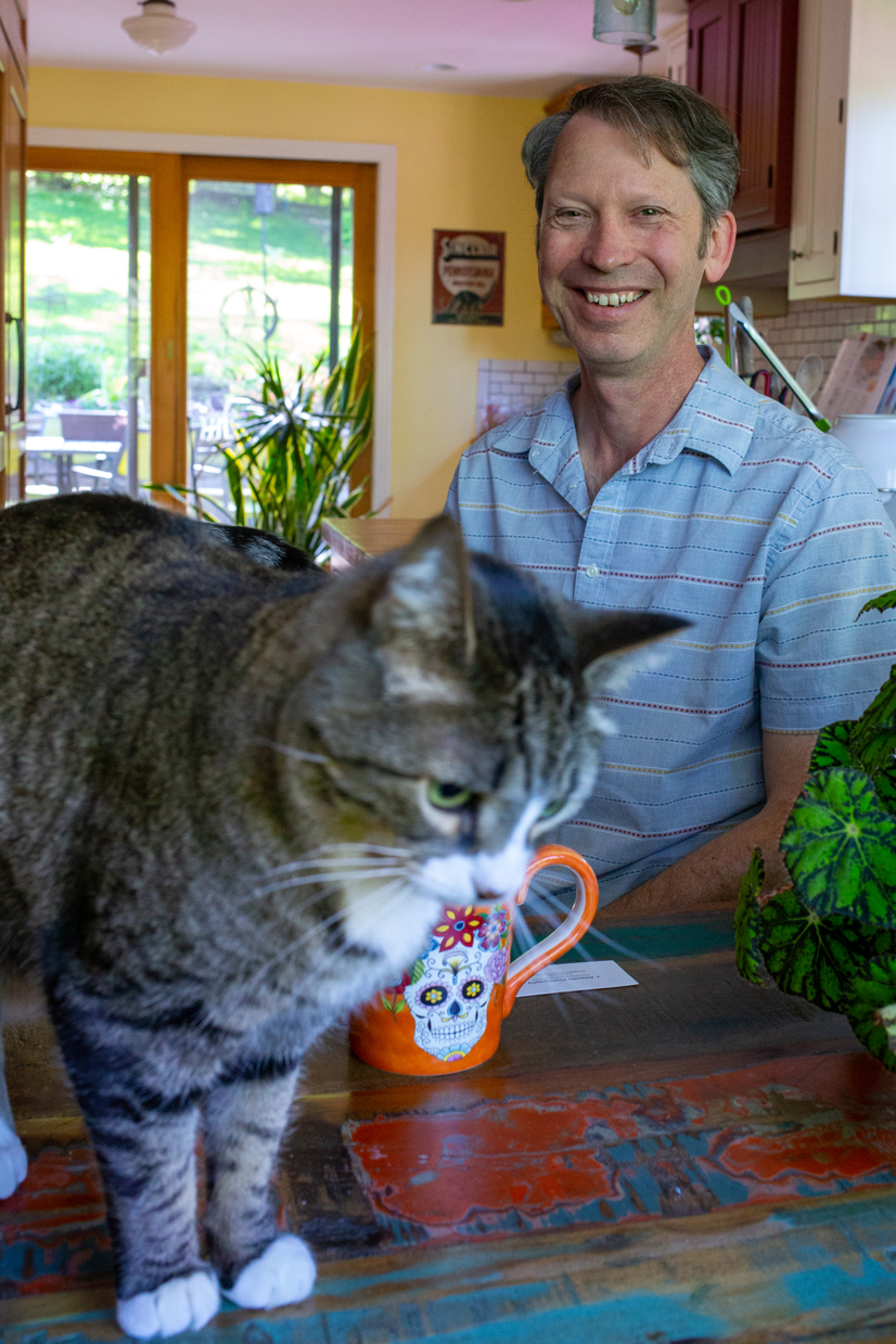 Charlie Jones with his cat and a coffee smiling.
