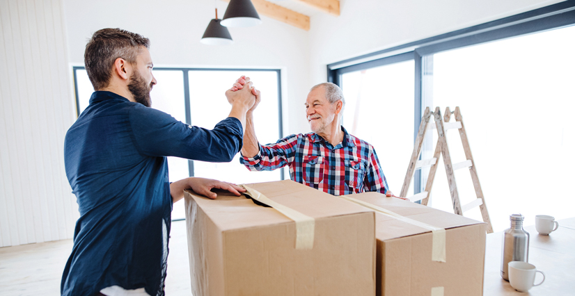 A man and his father joyfully packing boxes to move in an apartment.
