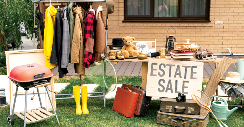 """some things layed out on a table, and clothes hung up on a rack with a sign that says """"estate sale""""."""