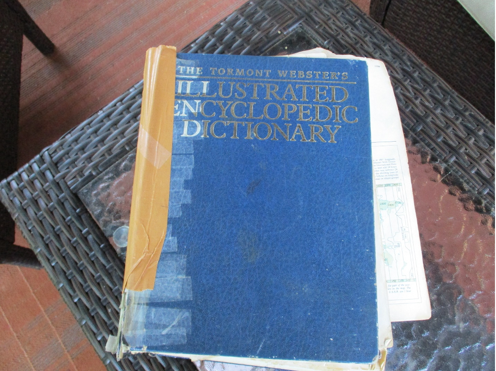 Blue Tormont Webster's Illustrated Encyclopedic Dictionary, ripped torn and taped along the spine after frequent use.