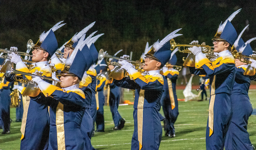Mt. Lebanon marching band, horn section, playing music on a football field.