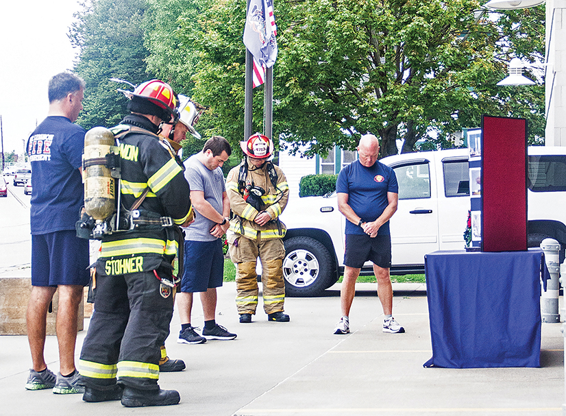 Firefighters stand with heads bowed in a moment of silence during last year's 9/11 Ceremony.