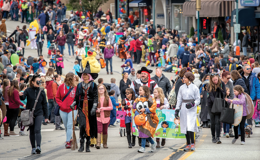 A Halloween costume parade, hudreds of people walking in the street dressed up in costumes.