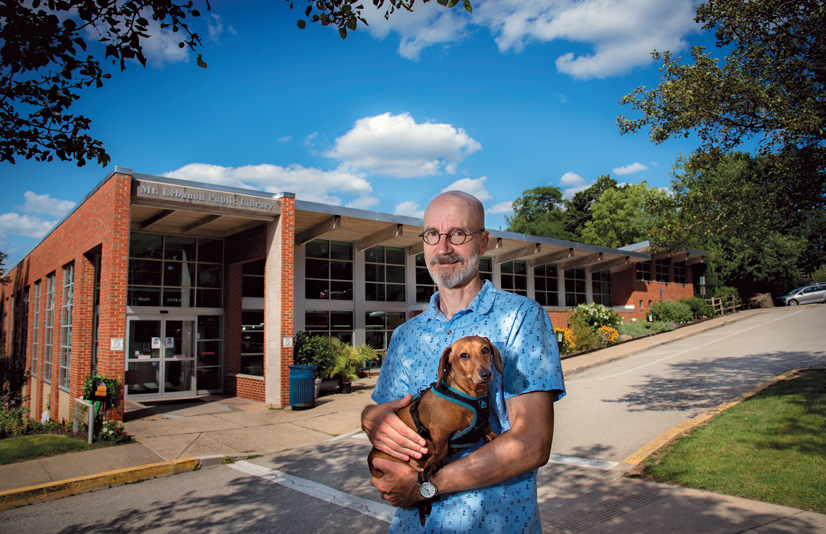 Bob Hagerty holding his dog standing in front of the Mt. Lebanon Library.