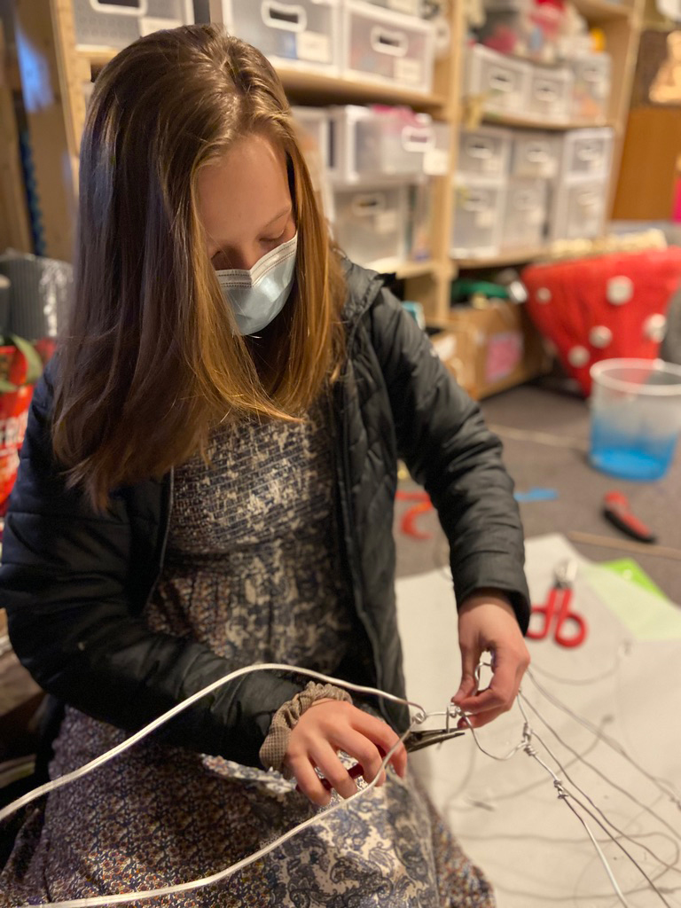 a middle school age girl using pliers building something out of wire.