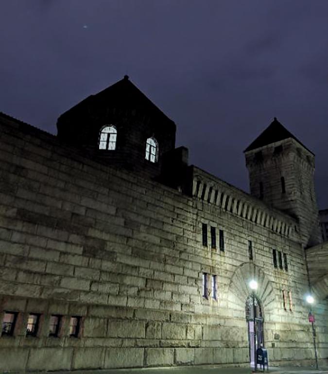 a poorly lit stone wall, photo taken at night.
