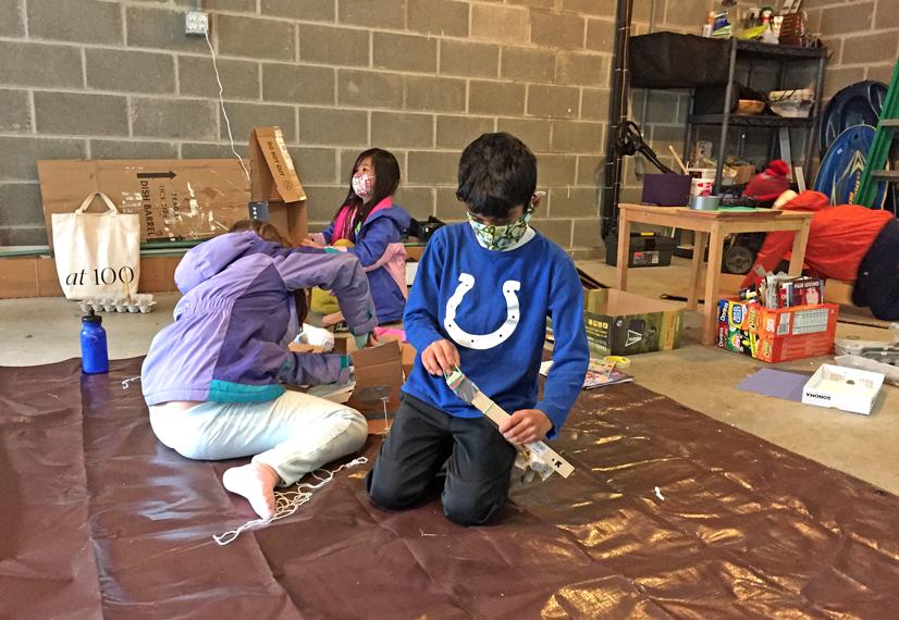Three grade school age kids in a garage building props.