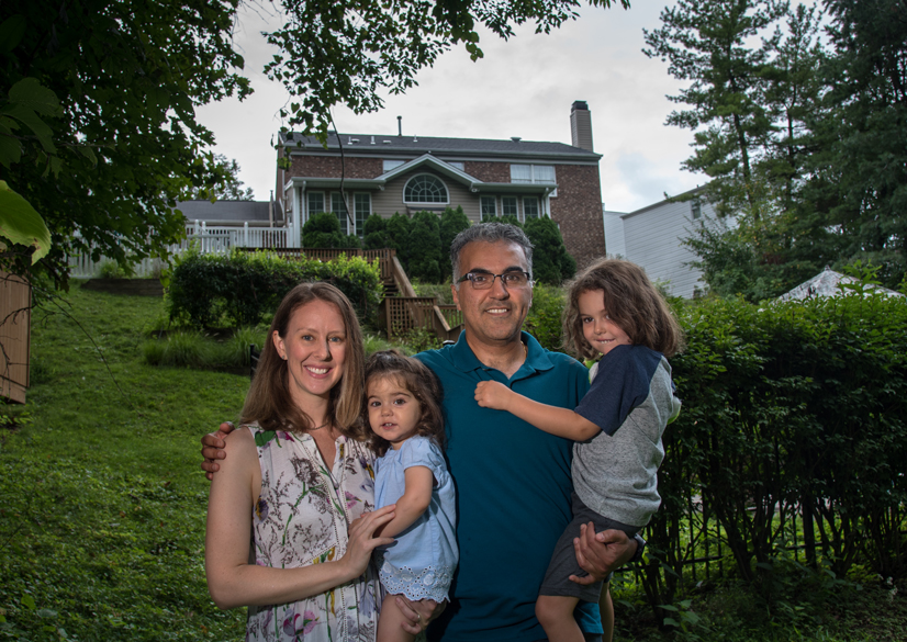 Whitney and Jalal standing in front of their house with their two kids.