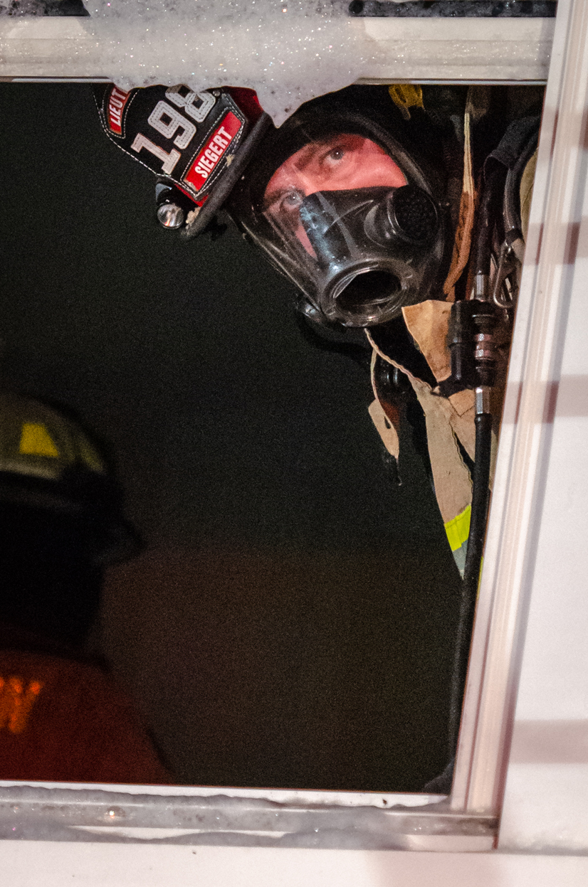 Kris Siegert peaking through a window wearing fire safety gear and a mask.
