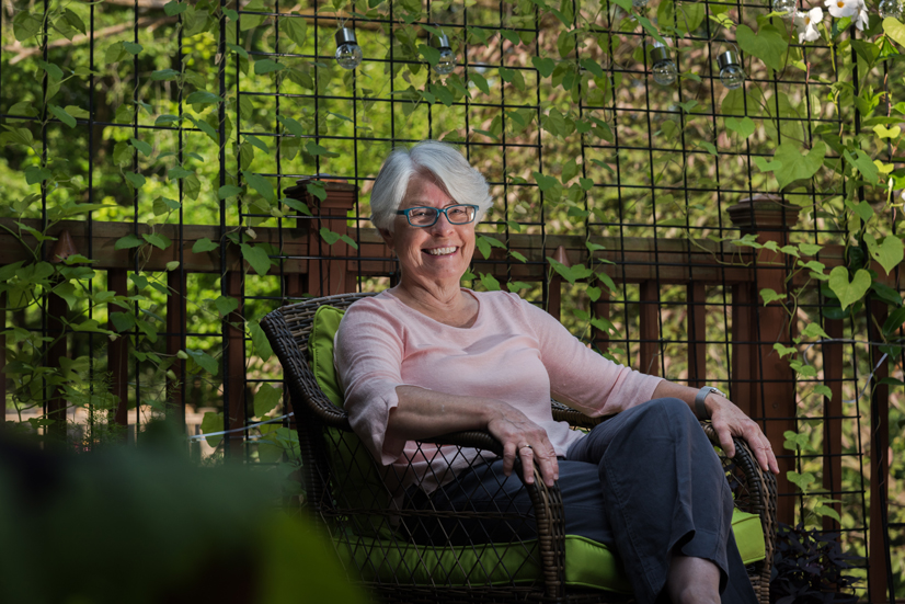 Linda Petrilli sitting on her porch surrounded by greenery.