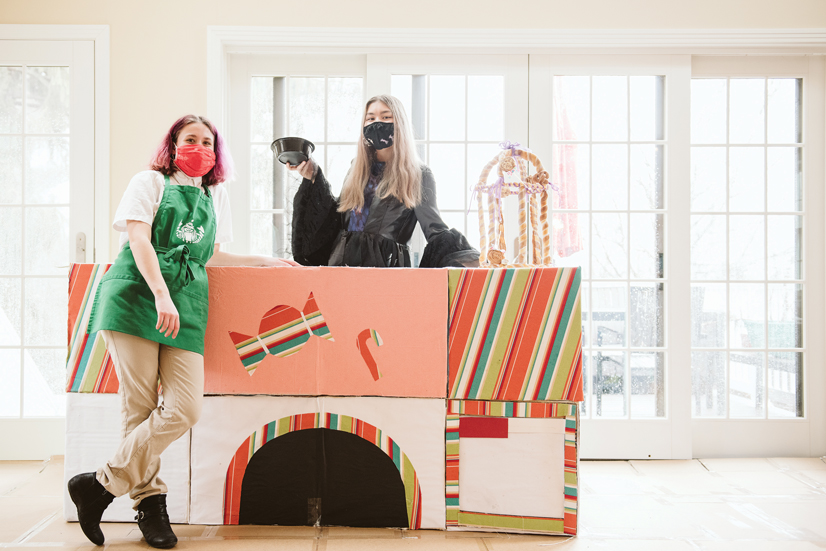 Two girls standing over a counter they built while dressed as baristas.