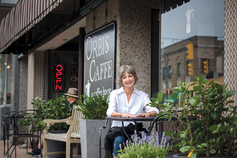 Sue Buse sitting at a table outside of Orbis Caffe.