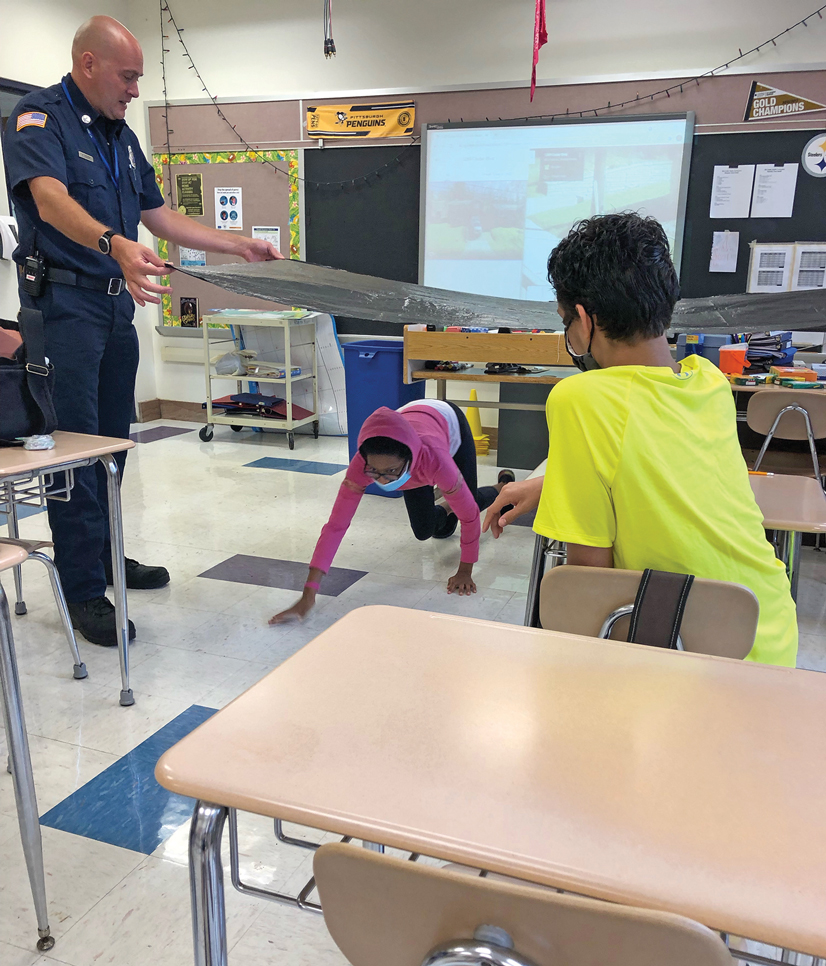 Kris Siegert in a classroom, holding black plastic as a child crawls underneath teaching about fire safety.